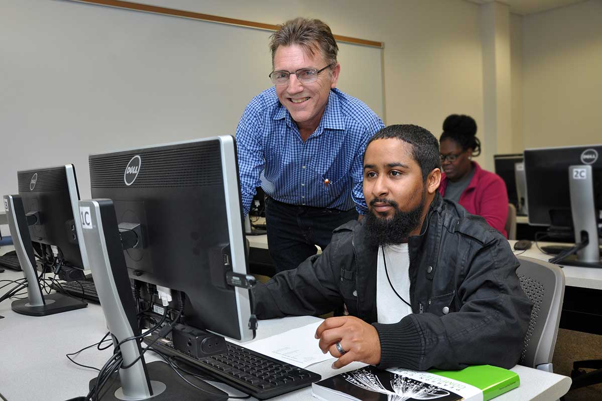 student and instructor at a computer
