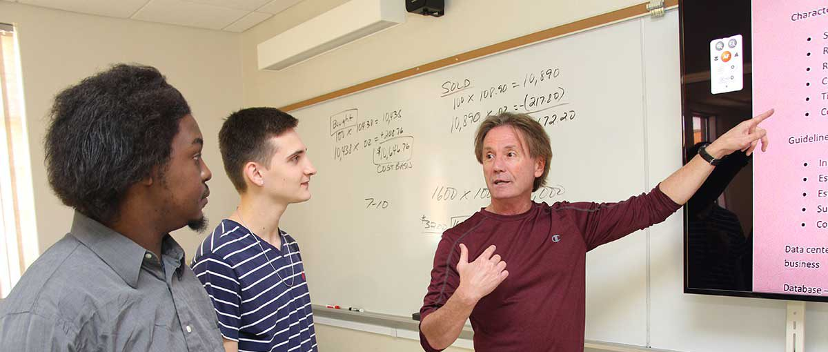 Instructor discussing concepts with students in class.