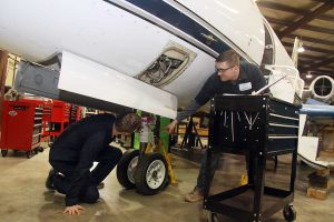 students performing maintenance on a plane