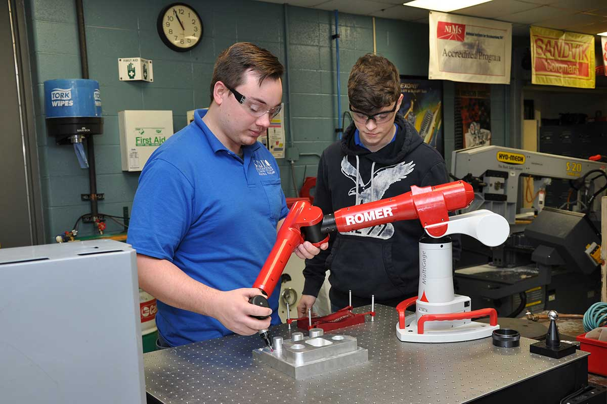 Students using a precision measuring device in the machining program