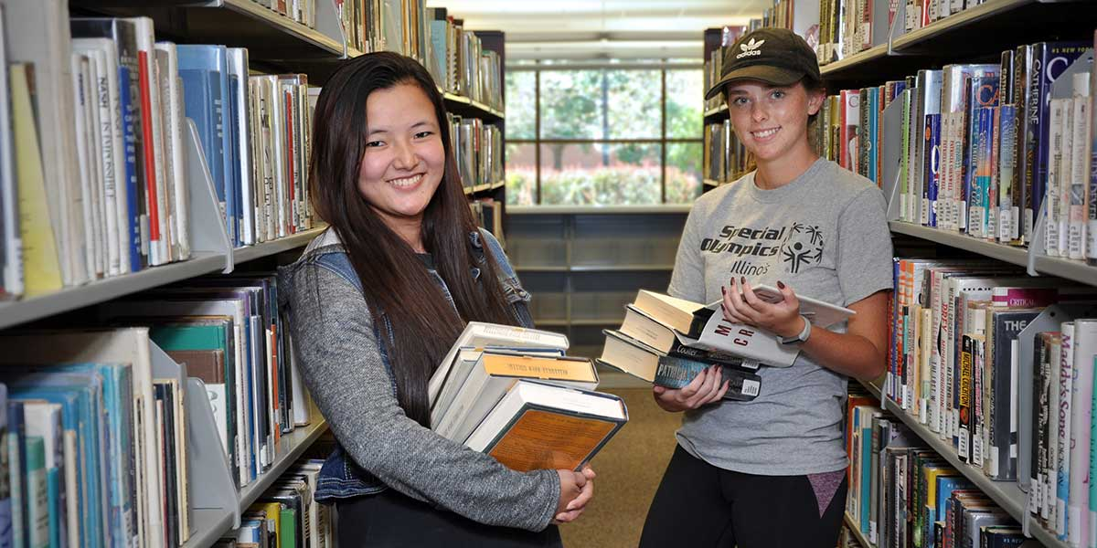 two girls holding books