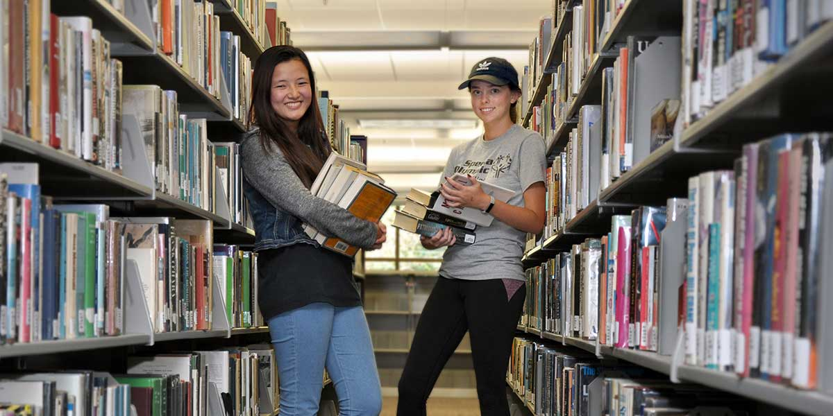 Library - two girls in aisle