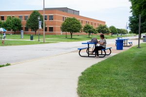 Photo of a woman sitting at a picnic table in front of the SWIC main complex.