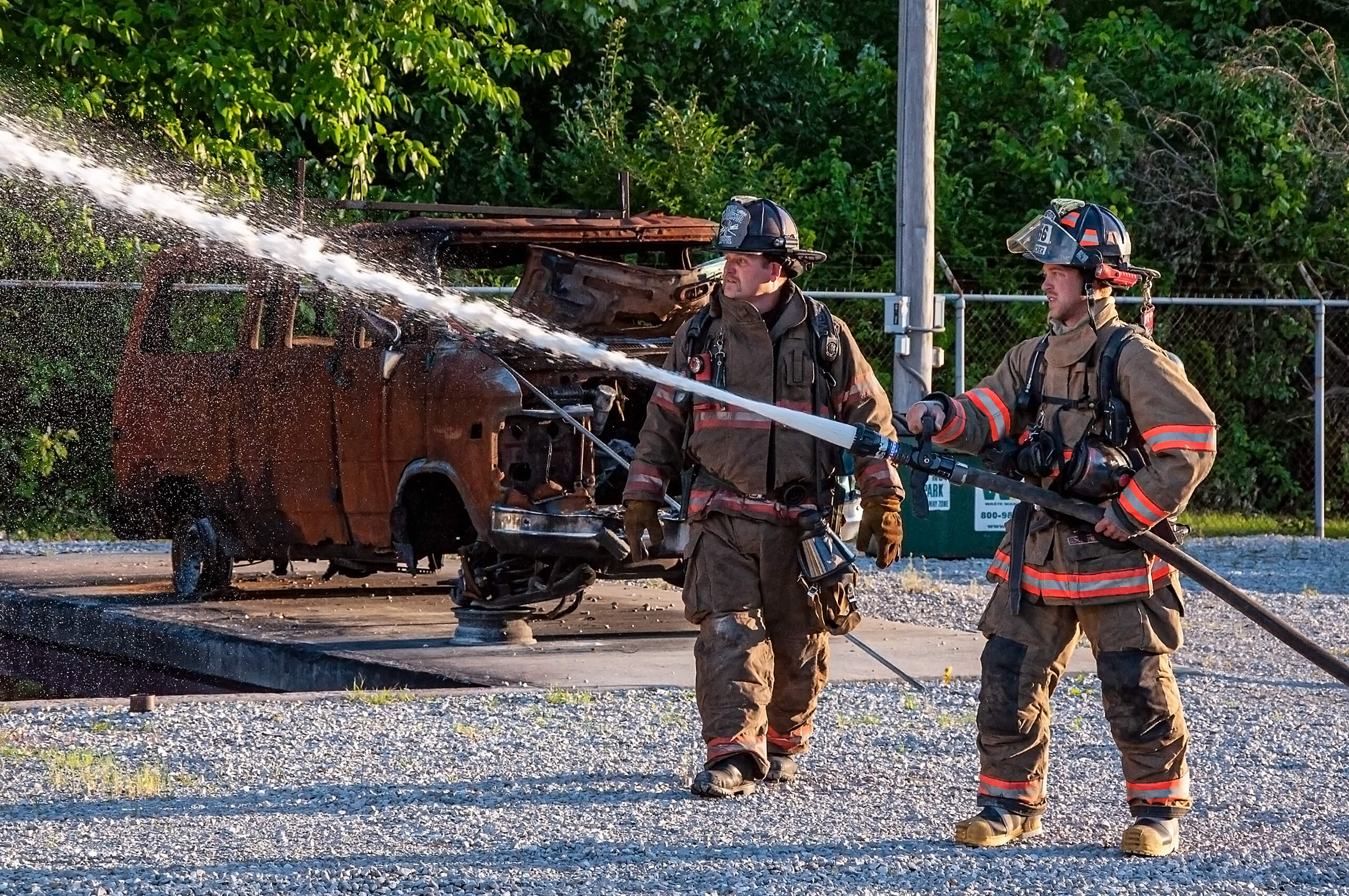 Fireman and trainer with fire hose preparing for a training exercise.
