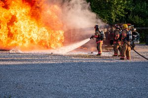 Three fire fighters putting out a fire during fire training exercises.