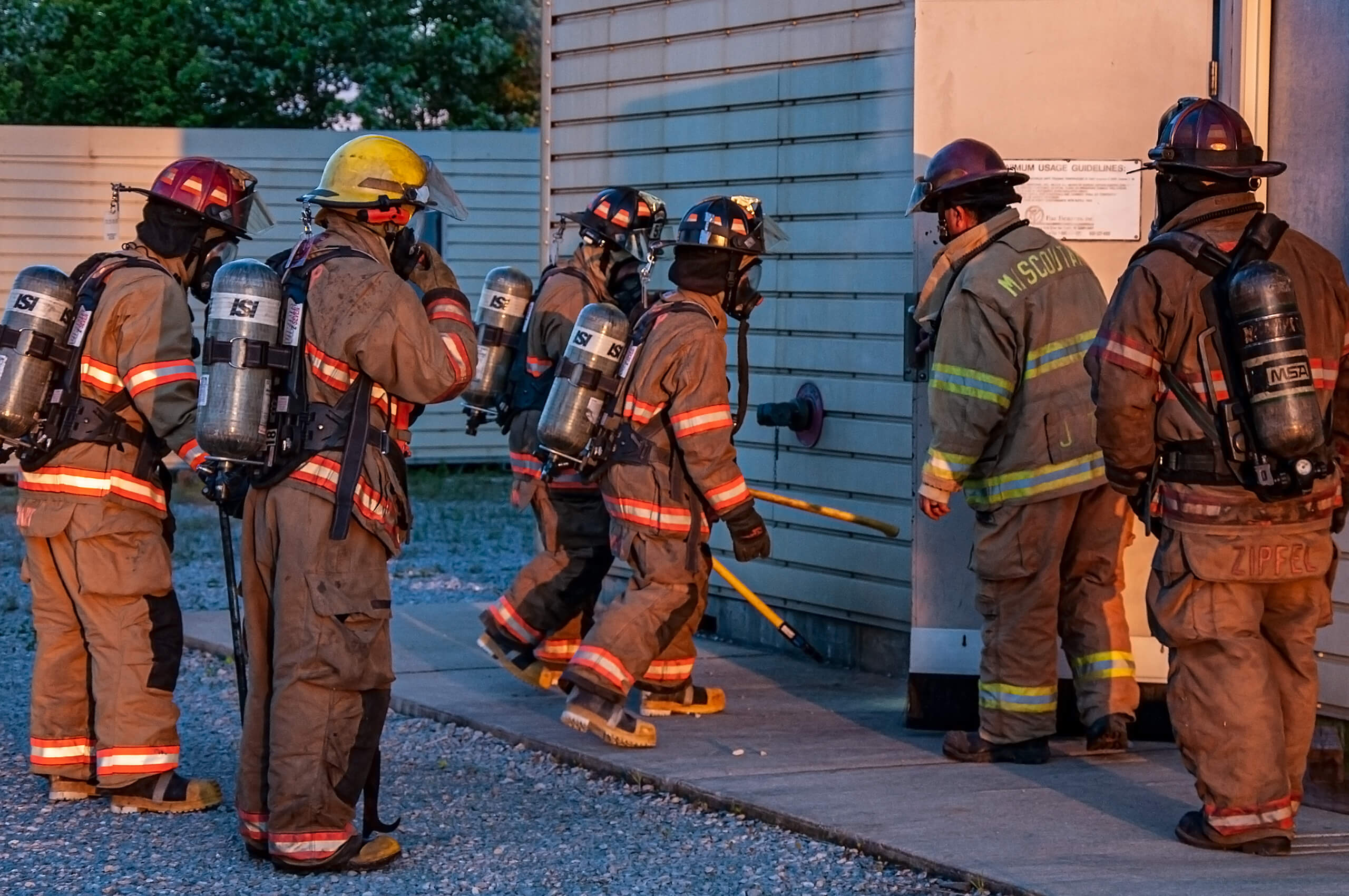 A group of firefighters entering a smoke filled building for a training exercise.