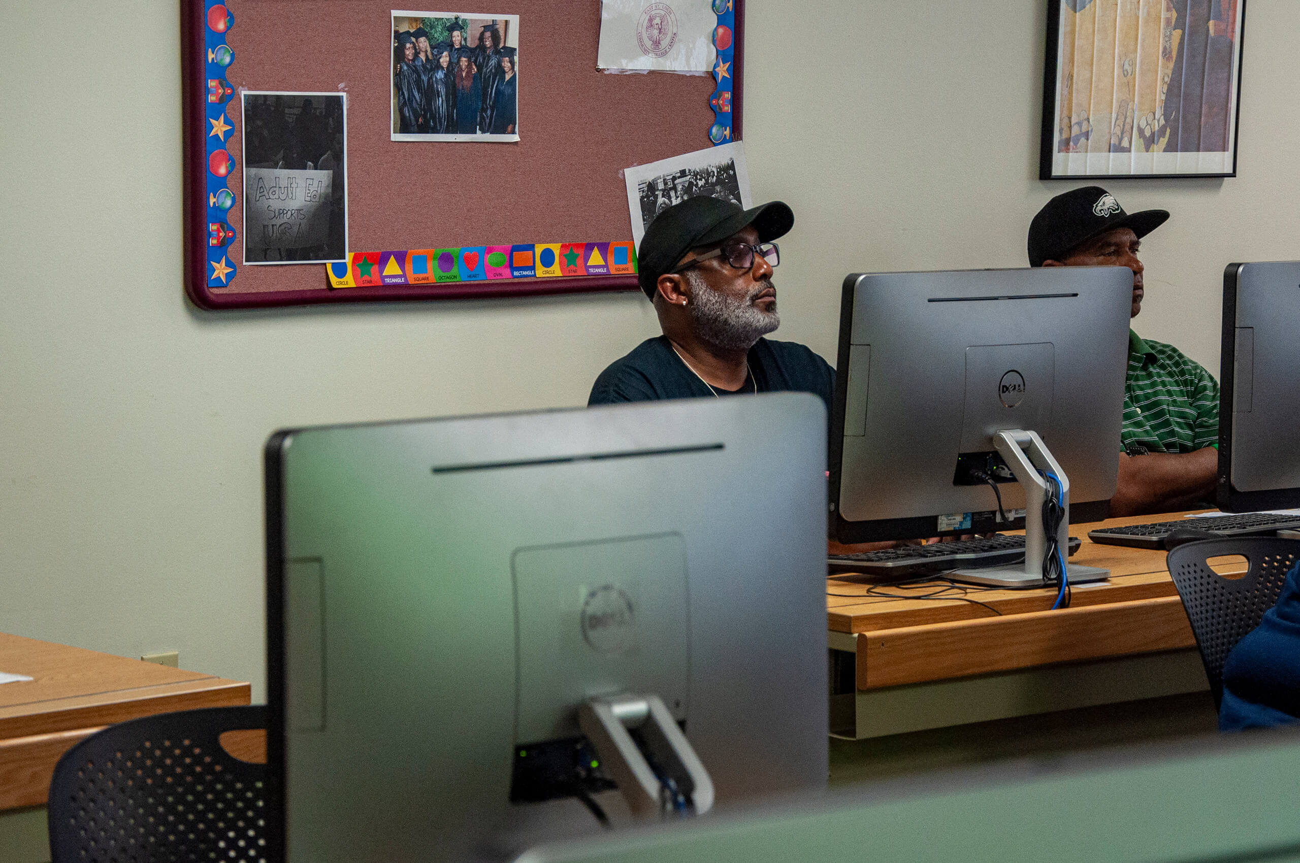 Photo of an older African American male sitting at a computer while listening to a lecture in a classroom.