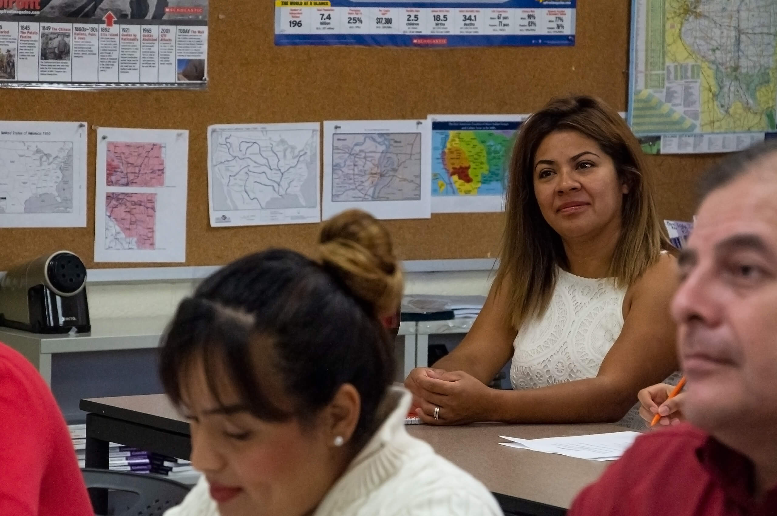 Photo of a woman smiling while paying attention to the instructor in an English as a Second Language course.