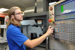 Precision Machining Technology student programming a CNC lathe.