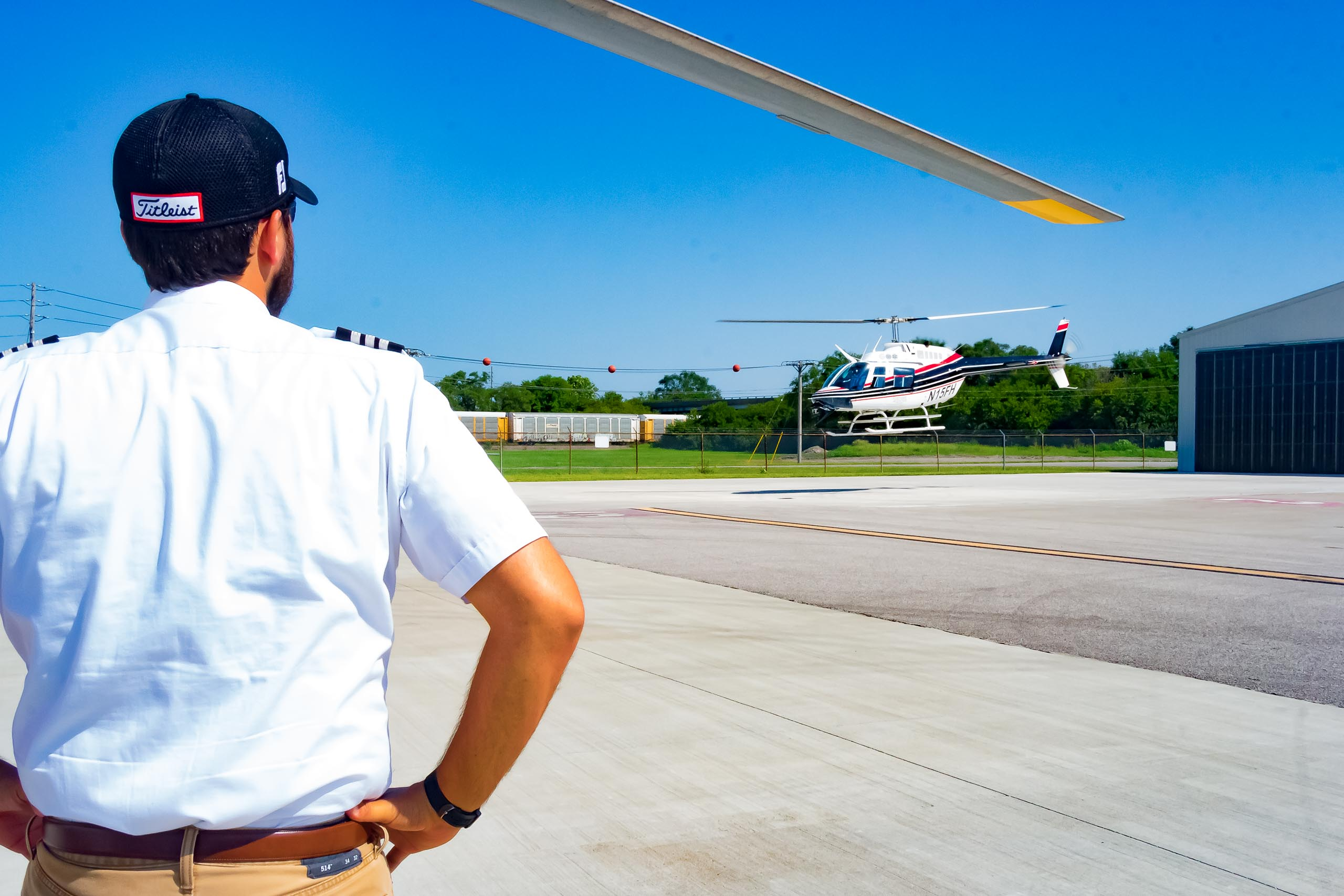 Helicopter landing with instructor watching.