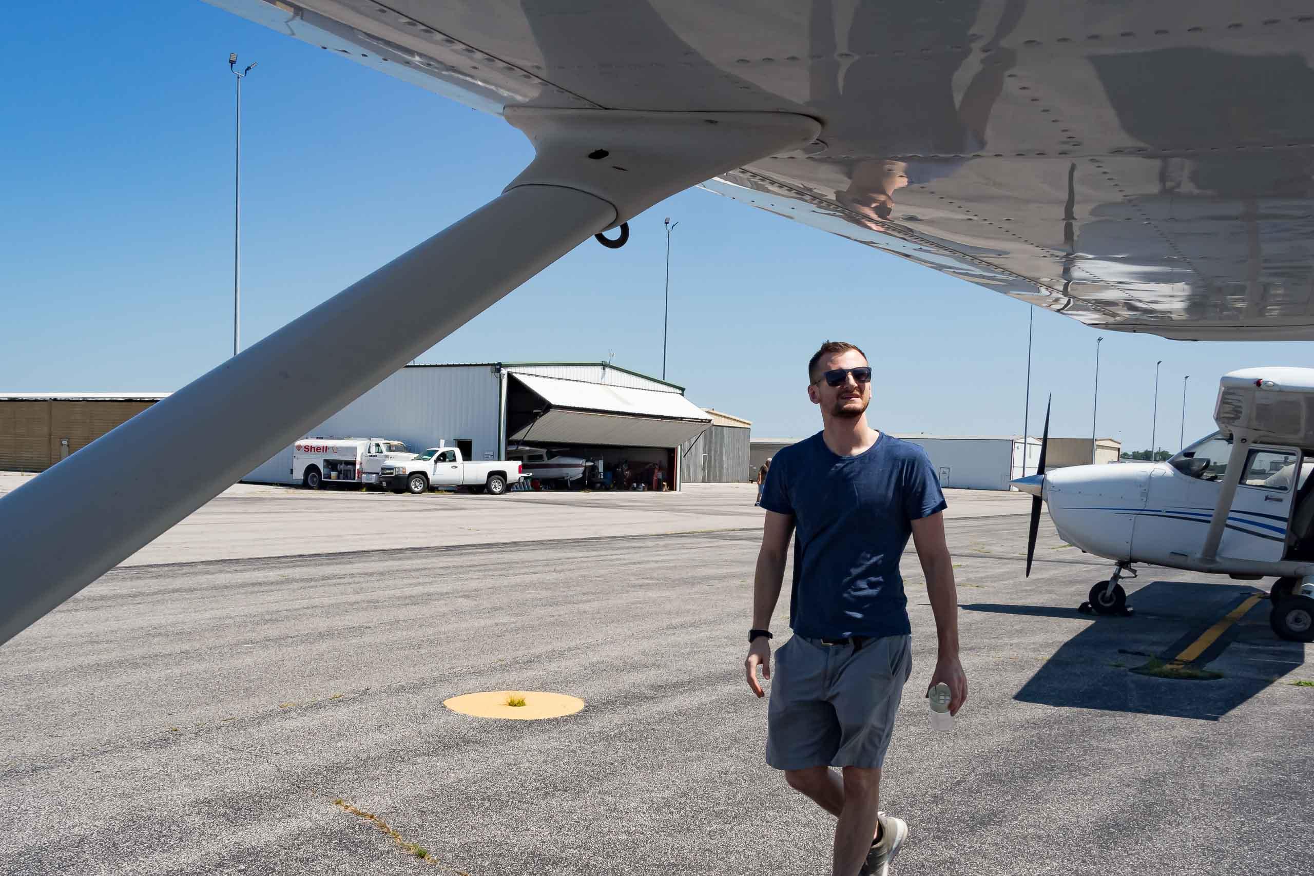 Student walking around airplane.