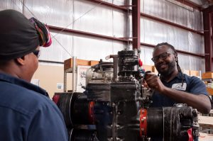 Aircraft Maintenance students working on engine.