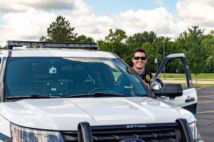 Officer beside patrol car.