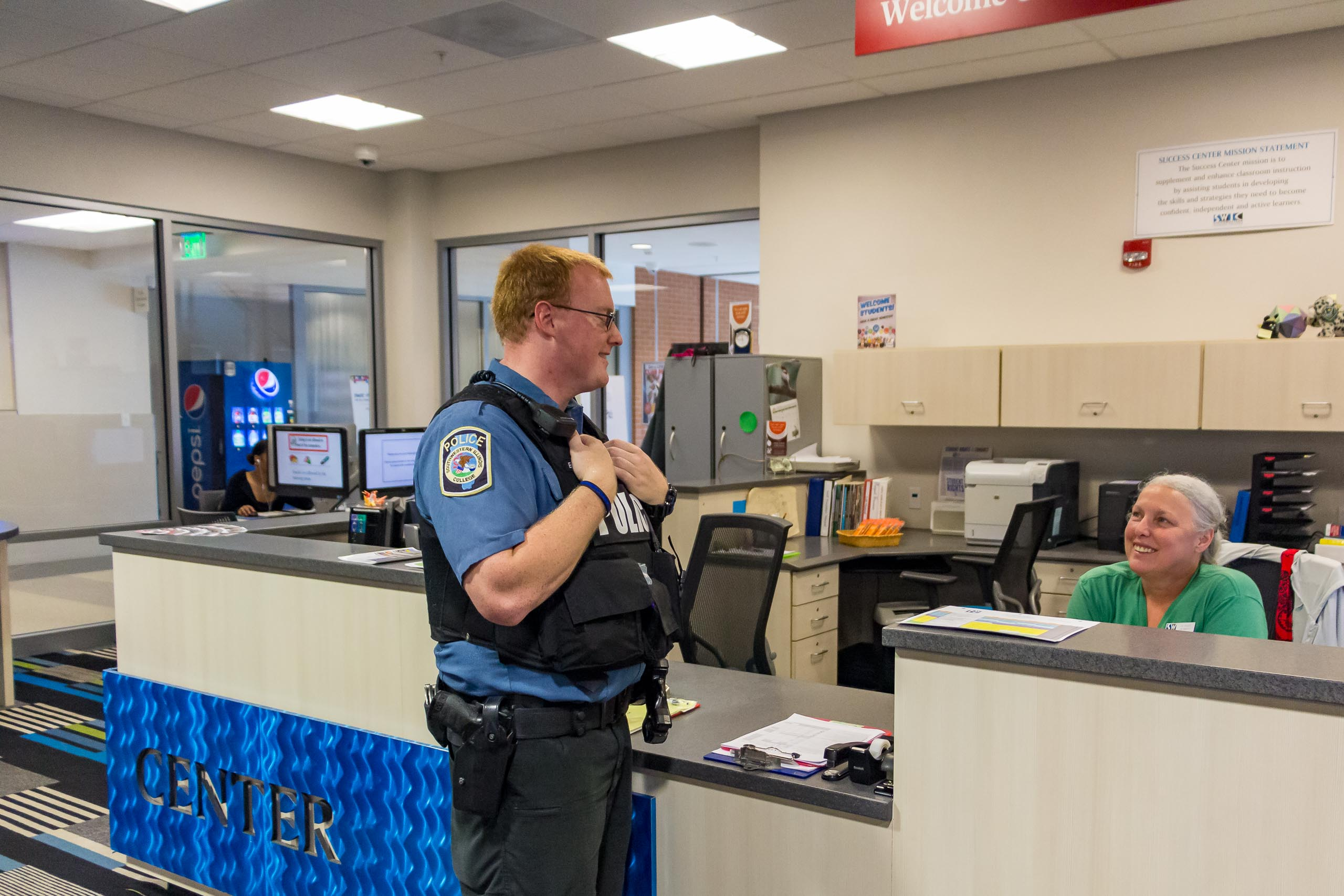 Officer speaking to Welcome Desk attendant in Success Center.