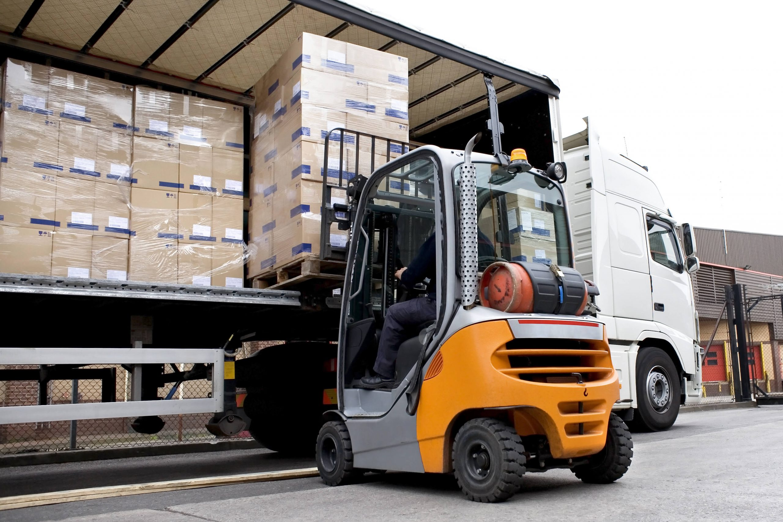 Warehouse and distribution file photo depicting offloading palatalized boxes with a forklift.