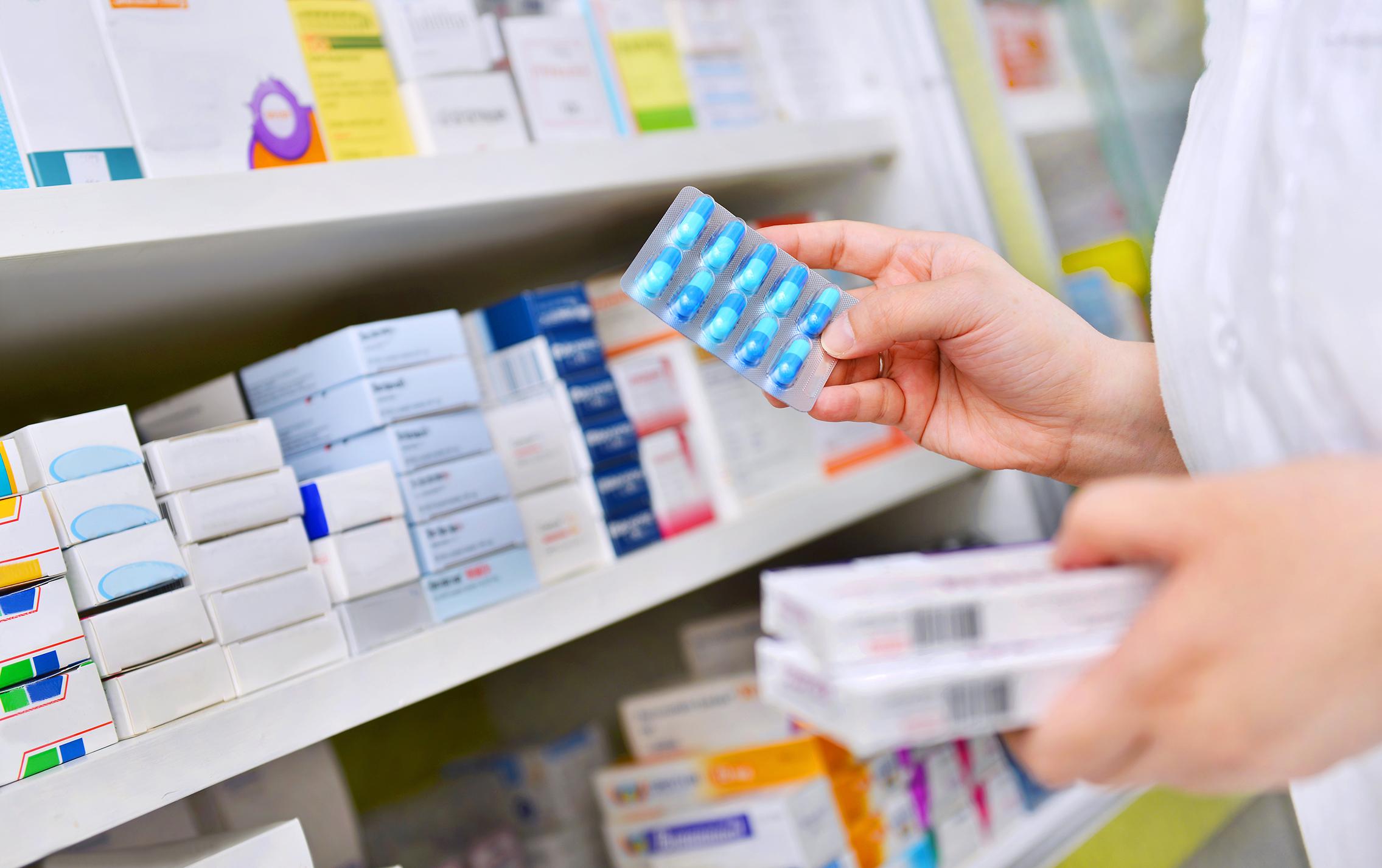 Pharmacist holding medicine box and capsule pack in pharmacy dru