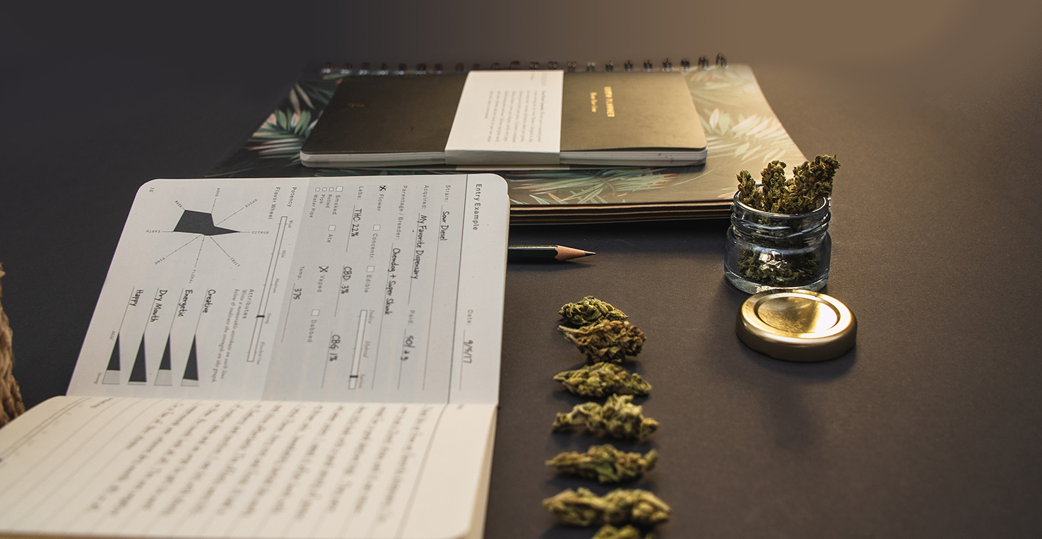 Cannabis bud lineup, stationery, joint, jar, pages on black back